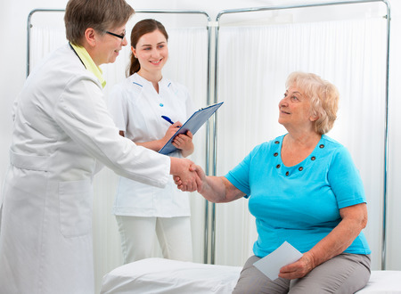 physician: Smiling doctor at the office giving a handshake to her patient
