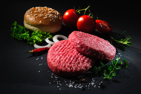 Homemade hamburger. Raw beef patties, sesame buns with other ingredients for hamburgers on dark slate plate Imagens