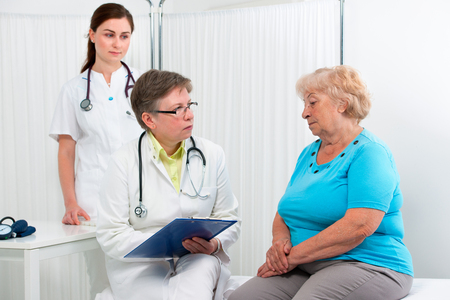 Physician explaining diagnosis to elderly patient at the office photo