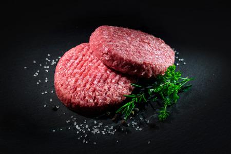 다크 슬레이트 접시에 향신료와 원시 쇠고기 햄버거 패티