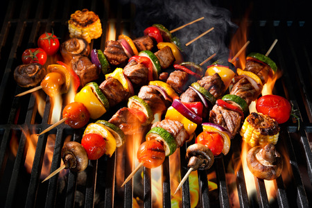 barbecuing: Barbecue skewers meat kebabs with vegetables on flaming grill