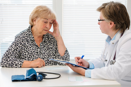 doctor burnout: Female senior patient tells the doctor about her health complaints
