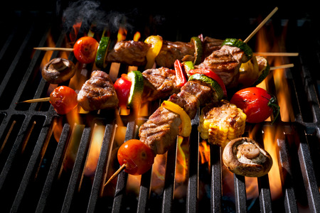 barbecue fire: Barbecue skewers meat kebabs with vegetables on flaming grill