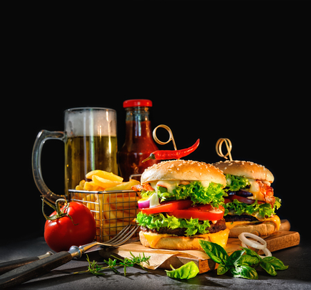 salsa de tomate: Delicious hamburgers with french fries and beer on dark background
