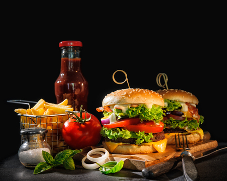 Delicious hamburgers with french fries and ketchup on dark background Stock Photo