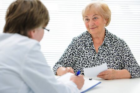 Female senior patient tells the doctor about her health complaints photo