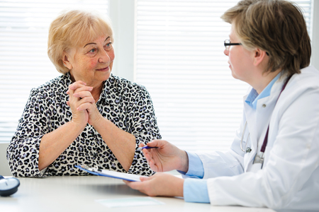 Female doctor explaining diagnosis to her senior patient photo