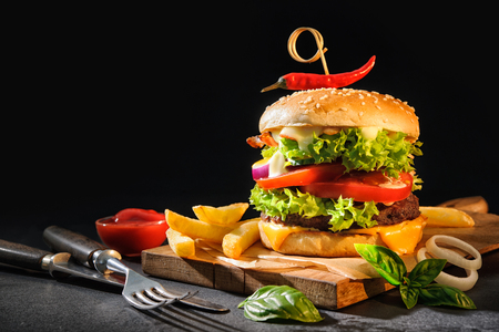Delicious hamburgers with french fries on dark background Stock Photo