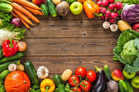 Frame of assorted fresh vegetables on wooden background