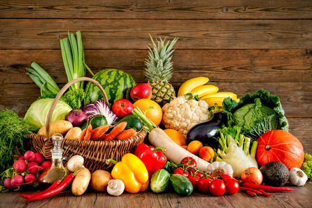 Assortment of the fresh fruits and vegetables on wooden background Stock Photo