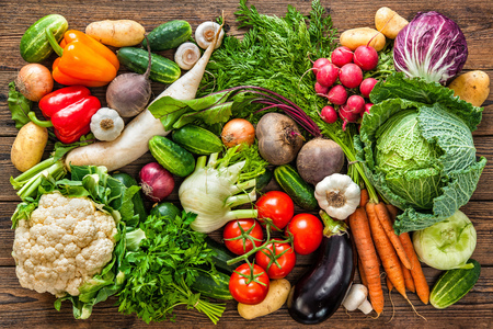 Assortment of the fresh vegetables on wooden background Imagens