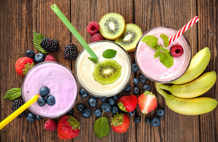 Healthy smoothies with fresh fruits on wooden table Stock Photo