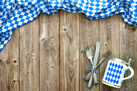 Rustic background for Oktoberfest with Bavarian white and blue fabric, beer stein and silverware Stock Photo