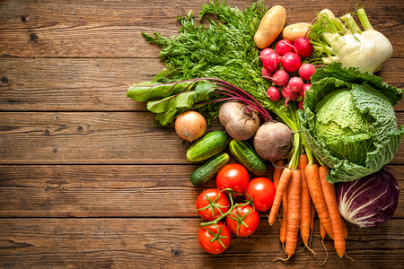 Assortment of the fresh vegetables on wooden background Stock Photo