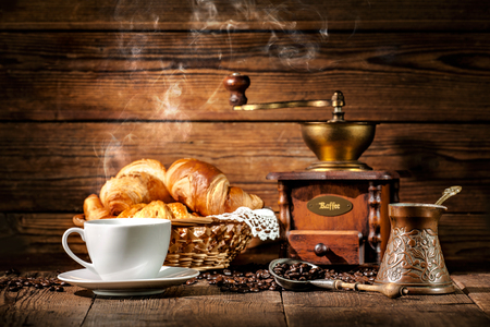 filiżanka kawy: Coffee cup with croissants and coffee beans on wooden background