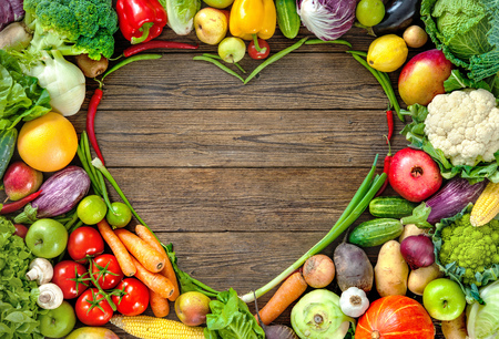 Assortment of  fresh fruits and vegetables in heart shape on wooden background Imagens