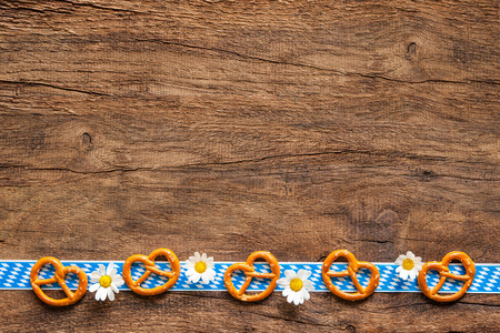 Border of pretzels and daisies with Bavarian ribbon on rustic wooden background with copy space for Oktoberfest