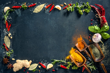 Herbs and spices over black stone background. Top view with copy space