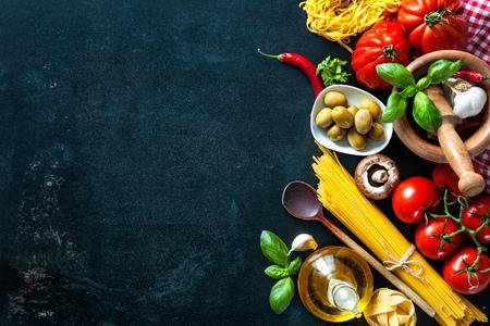 Italiaanse keuken. Groenten, olie, kruiden en deegwaren op een donkere achtergrond