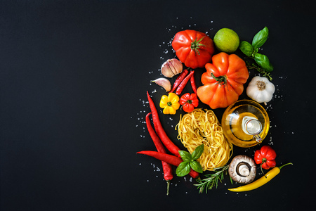 Italian cuisine. Vegetables, oil, spices and pasta on dark background Фото со стока - 62207382