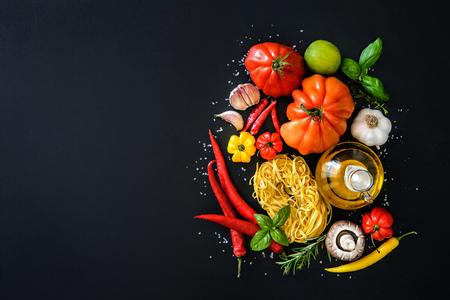 Italienische Küche. Gemüse, Öl, Gewürze und Teigwaren auf dunklem Hintergrund Standard-Bild - 62207382