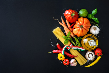 green pepper: Italian cuisine. Vegetables, oil, spices and pasta on dark background