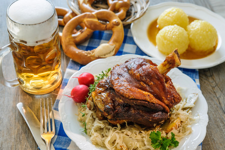 Appetizing Bavarian roast pork knuckle with dumplings and sauerkraut. Oktoberfest Stok Fotoğraf - 62207394