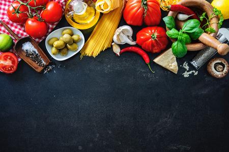 Italienische Küche. Gemüse, Öl, Gewürze und Teigwaren auf dunklem Hintergrund