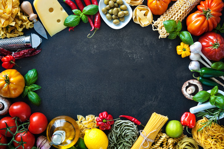 Italienische Küche. Gemüse, Öl, Gewürze und Teigwaren auf dunklem Hintergrund Standard-Bild - 62207388