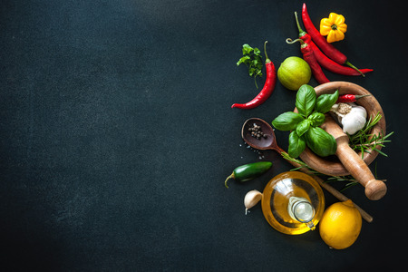 Herbs and spices with olive oil on slate background Stock Photo