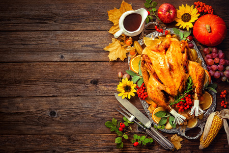 Thanksgiving diner. Geroosterde kalkoen met pompoenen en zonnebloemen op houten tafel