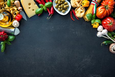 イタリア料理。野菜、油、スパイス、暗い背景上のパスタ