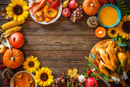 Thanksgiving dinner. Roasted turkey with pumpkins and sunflowers on wooden table Stock Photo