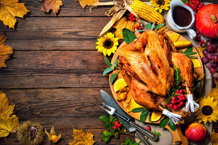 Thanksgiving dinner. Roasted turkey with pumpkins and sunflowers on wooden table Stock Photo - 62168946
