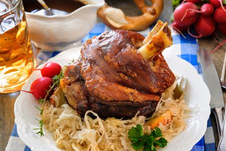 Appetizing Bavarian grilled pork knuckle with sauerkraut. Oktoberfest