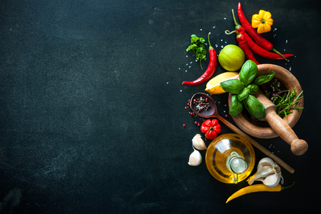 Herbs and spices with olive oil on slate background Archivio Fotografico