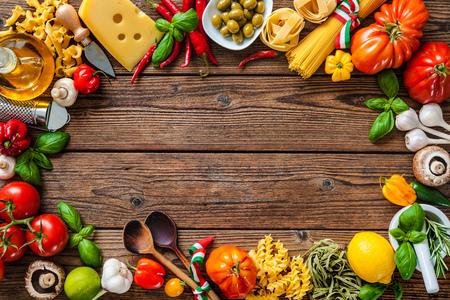 イタリア料理。野菜、油、スパイス、木製のテーブルにパスタ