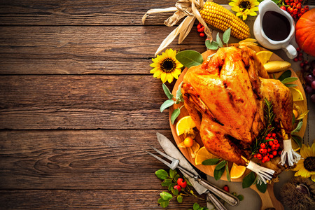 Cena de Acción de Gracias. pavo asado con las calabazas y los girasoles en la mesa de madera Foto de archivo - 62207624