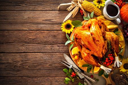 Festessen zum Erntedankfest. Gebratener Truthahn mit Kürbis und Sonnenblumen auf Holztisch