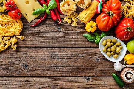 Cocina italiana. Verduras, aceite, especias y pastas en la mesa de madera