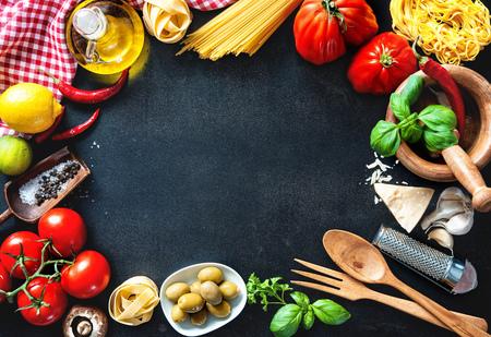 Italienische Küche. Gemüse, Öl, Gewürze und Teigwaren auf dunklem Hintergrund Standard-Bild - 62207725
