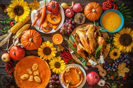 fall leaf: Thanksgiving dinner. Roasted turkey with pumpkins and sunflowers on wooden table