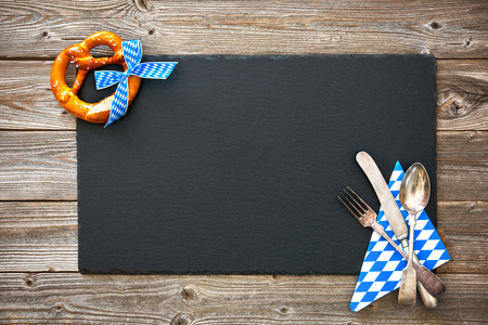 table setting: Bavarian pretzel with ribbon and silverware on wooden board. Background for Oktoberfest