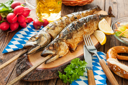 smoked: Oktoberfest menu. Grilled mackerel fish with beer and pretzel served on table