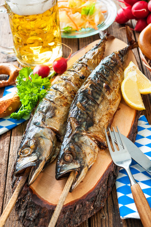 Oktoberfest menu. Grilled mackerel fish with beer and pretzel served on table