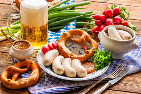Traditional Bavarian meal. White sausages with sweet mustard and pretzel Фото со стока