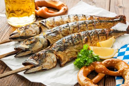 Oktoberfest menu. Grilled mackerel fish with beer and pretzel served on table