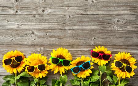 Zonnebloemen met zonnebril op houten bord Stockfoto