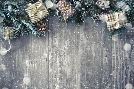 new years vacation: Christmas background with decorations and gift boxes on wooden board