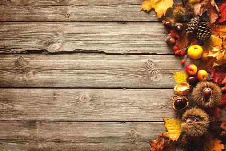 落とされた葉および古い木製のテーブルの上の果物からヴィンテージの秋ボーダー。感謝祭秋背景